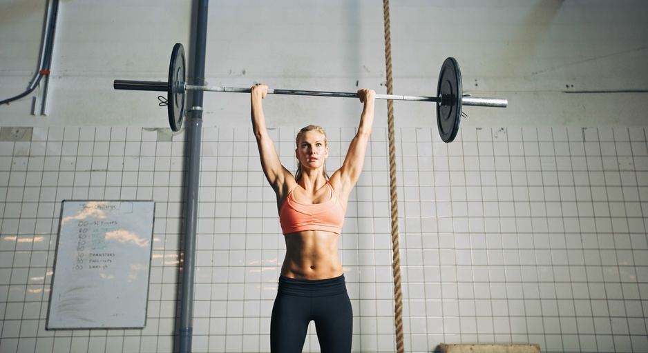 Fitness woman lifting barbells